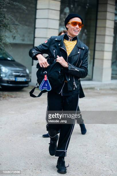 Model Adwoa Aboah exits the Dior show in red sunglasses a black leather jacket black bag with an 'A' keychain black pants and black Reebok sneakers...