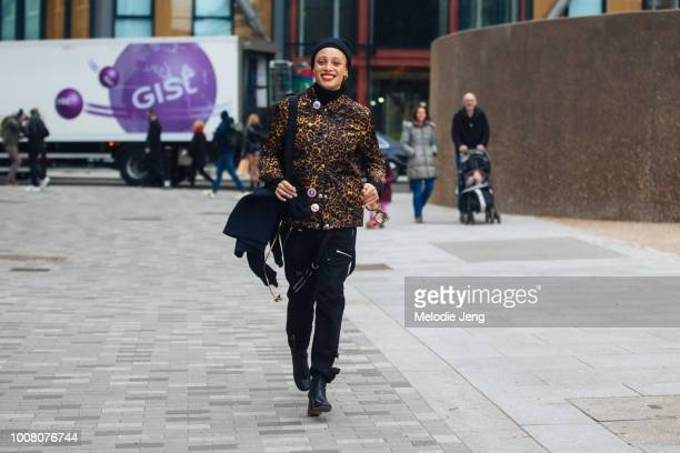 Model Adwoa Aboah exits the Topshop show at Tate Modern in a black beanie leopard print jacket Gurls Talk pins black pants and black boots on Day 3...