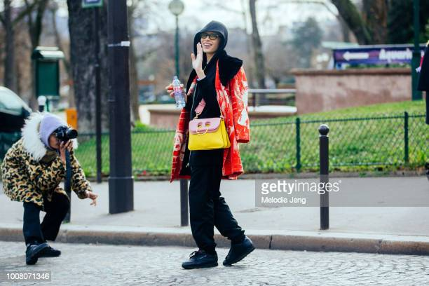 Model Adwoa Aboah waves after the Miu Miu show and wears a red print jacket black hoodie yellow and pink JW Anderson Pierce purse and black Reebok...