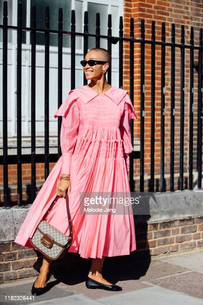 Model Adwoa Aboah wears a pink pleated dress Gucci bag and black ballerina flats after the Molly Goddard show during London Fashion Week September...
