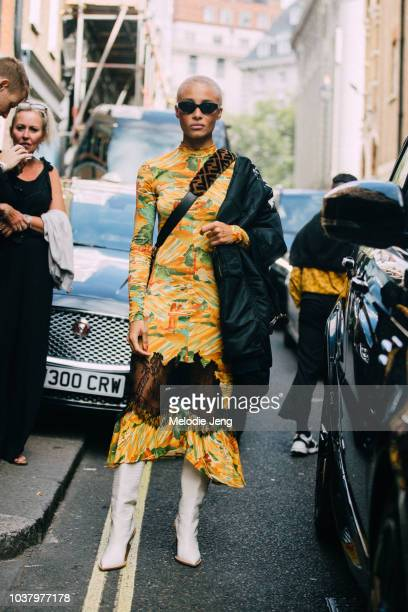 Model Adwoa Aboah wears black sunglasses a Fendi fur crossbody bag yellow print dress white boots and a bomber jacket on one shoulders after the...
