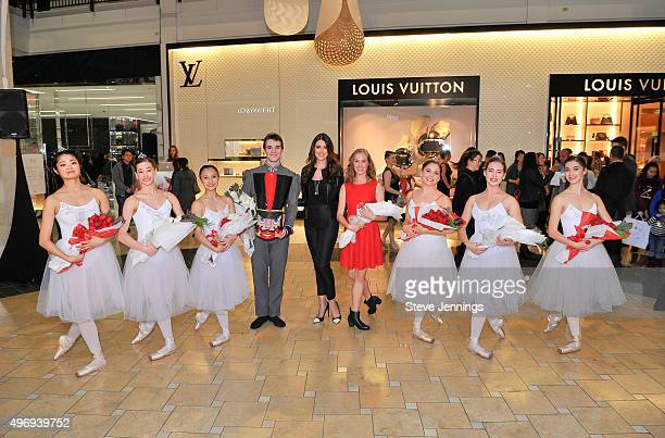 model Agatha Relota Luczo poses with the Silicon Valley Ballet dancers at Westfield Valley Fair on November 12 2015 in Santa Clara California