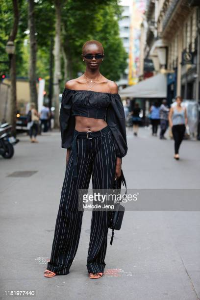 Model Akiima wears skinny black sunglasses an offshoulder cropped black top black striped pants and a black bag after the Schiaparelli show during...