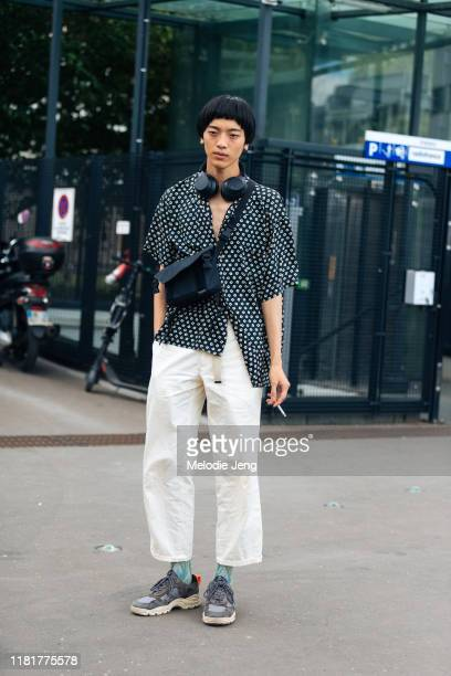 Model Akito Mizutani wears black headphones a black bagjack bag black print buttonup shirt white pants and purple Filling Pieces sneakers after the...