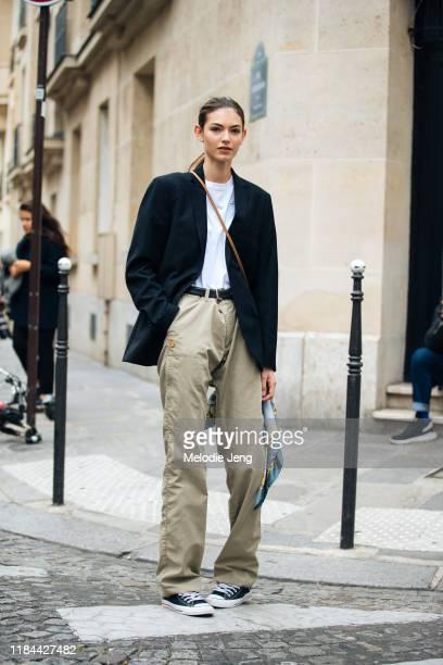 Model Alberte Mortensen wears a black oversized blazer, white Kappa t-shirt, khaki pants, and black Converse sneakers after the Altuzarra show during...