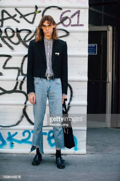 Model Aleksandr Gordeev exits the Acne Studios show in yellow tinted sunglasses a cropped pinstripe blazer with a floral brooch a blue striped top...