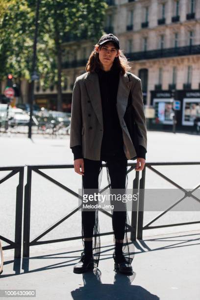 Model Aleksandr Gordeev wears a black Archive cap oversized gray blazer black shirt black leggings and chiffon black shoes during Paris Fashion Week...