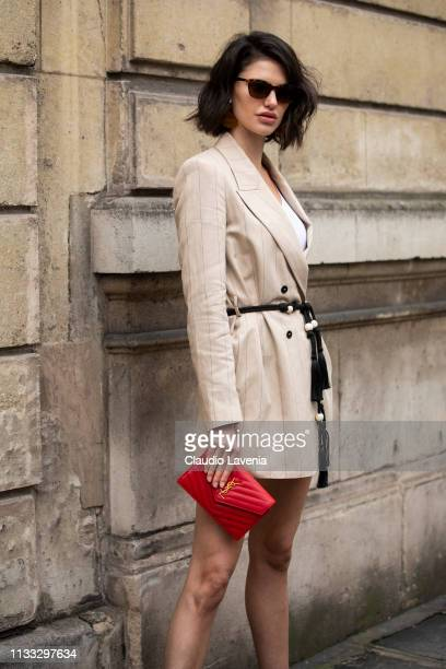 Model Alex Binaris wearing a cream striped blazer with a black belt and a red Saint Laurent bag is seen outside Elie Saab on Day 6 Paris Fashion Week...