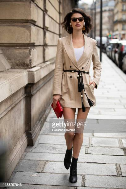 Model Alex Binaris wearing a cream striped blazer with a black belt black boots and a red Saint Laurent bag is seen outside Elie Saab on Day 6 Paris...