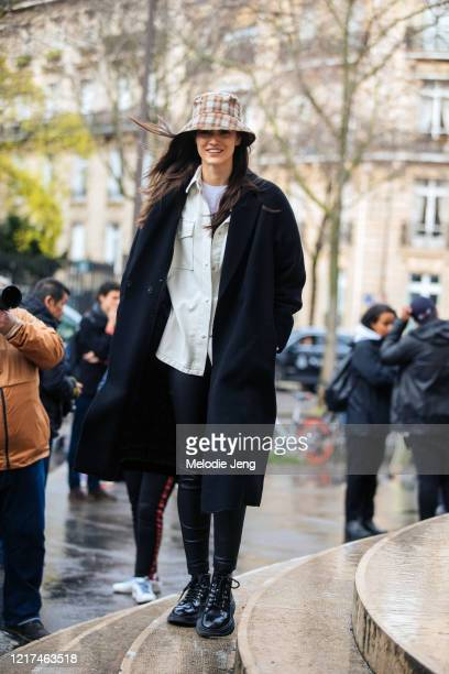 Model Alexander Micu wears a red plaid bucket hat, black coat, white shirt, black leather pants, and black boots after the Akris show during Paris...