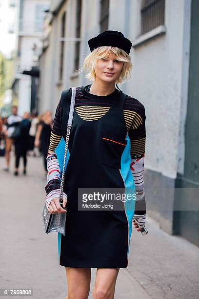 Model Alexandra Elizabeth Ljadov wears a hat a colorblocking black dress over a multicolored striped sweater and a silver Dior Diorama bag after the...