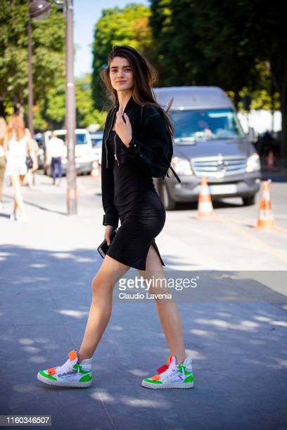 Model Alexandra Micu, wearing a black dress, black denim jacket and colorful Off-White sneakers, is seen outside Alexandre Vauthier show during Paris...