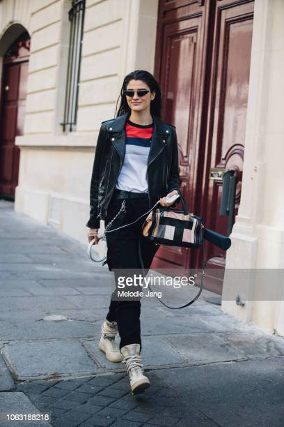 Model Alexandra Micu wears a black leather jacket Coach bag black pants and suede wrap sneakers after the Altuzarra show during Paris Fashion Week...