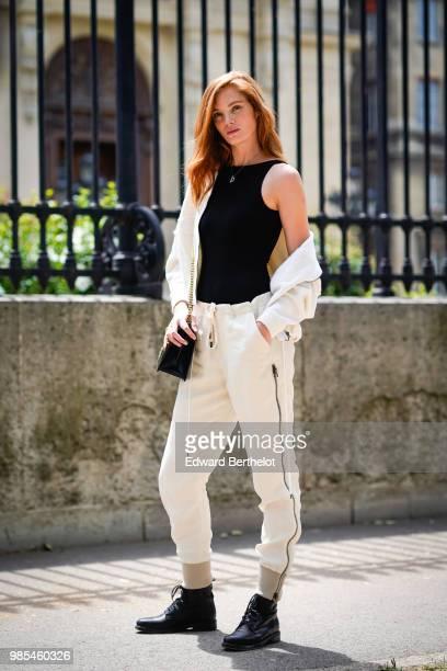 Model Alexina Graham wears a black top white pants a white jacket a bag black shoes outside Balmain during Paris Fashion Week Menswear SpringSummer...