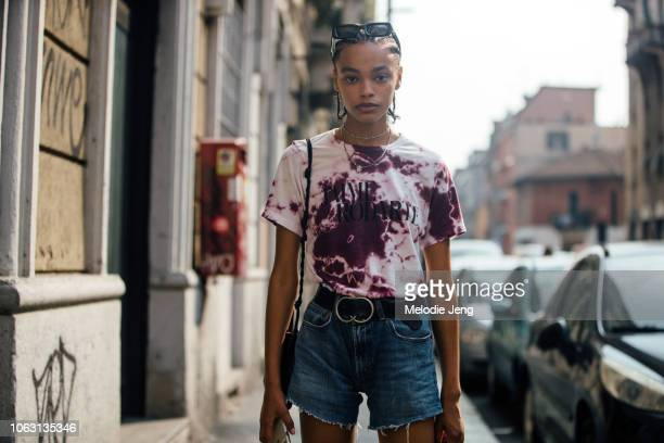 "Model Alexis Sundman wears a purple tie-dye ""J'aime Rodarte"" t-shirt, denim shorts during Milan Fashion Week Spring/Summer 2019 on September 19, 2018..."