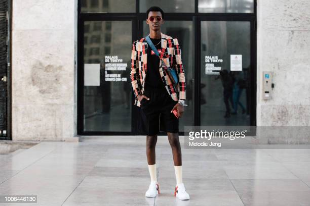 Model Alioune Badara Fall exits the Juun J show in red sunglasses a red checkered blazer Supreme tshirt Louis Vuitton monogram leather crossbody bag...