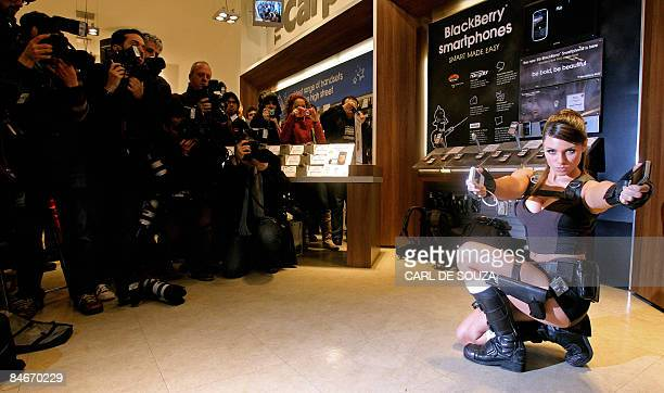 Model Alison Carroll poses with mobile phones as film and computer games character Lara Croft during a photocall in London on February 6 2009 The...
