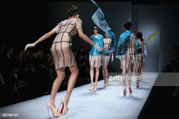 A model almost falls as models showcasing designs on the runway at SECCRY Hu Sheguang Collection 2014 Show during MercedesBenz China Fashion Week...