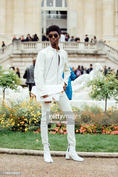 Model Alton Mason attends the Margiela show in black sunglasses a white leather jacket a white folded bag white skinny jeans and white Margiela tabi...