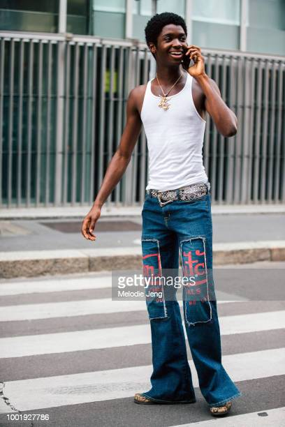 Model Alton Mason talks on the phone and wears a white tanktop gold angel necklace and blue Von Dutch jeans during Milan Men's Fashion Week...