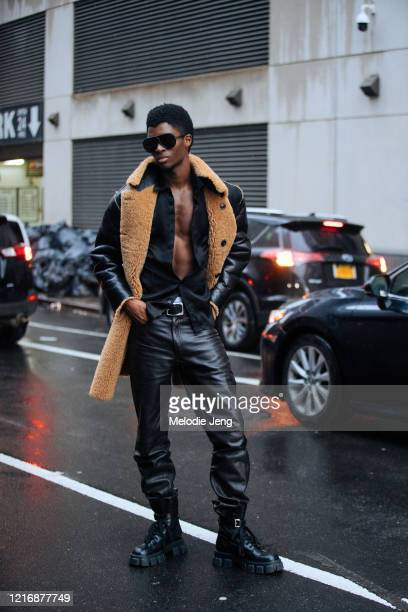 Model Alton Mason wars a black shearling jacket open black shirt black leather pants and black chunky Prada boots after the Dion Lee show on February...
