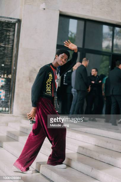 Model Alton Mason waves goodbye and wears a Paccbet/Rassvet sweater by Gosha Rubchinskiy Tolia Titaev plum purple pants and white sneakers after the...