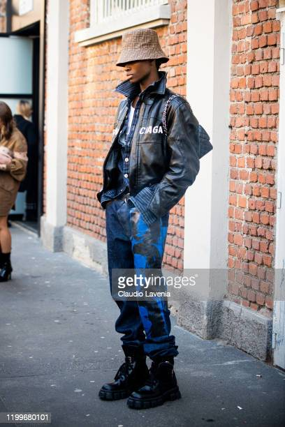 Model Alton Mason wearing a black leather Balenciaga jacket blue printed jeans black boots and Fendi hat is seen outside the Fendi show during the...
