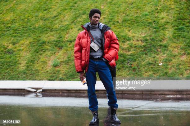 Model Alton Mason wears a red Vetements puffer jacket gray top Gucci logo bag across his body jeans black boots and a Moschino cigarette phone case...