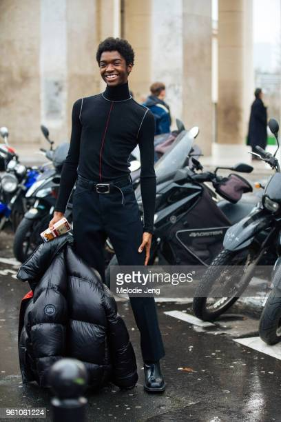 Model Alton Mason wears an all black outfit including a fitted turtleneck Canada Goose puffer jacket and a Moschino cigarette phone case during Paris...