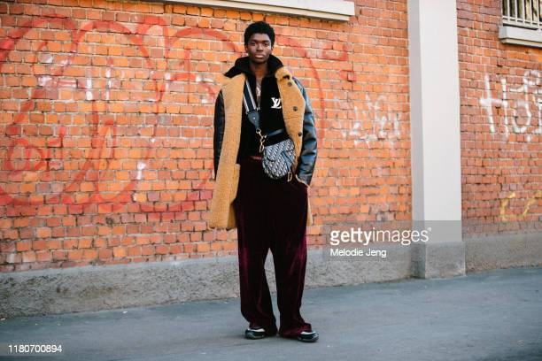 Model Alton Mason wears and long black shearling coat, Louis Vuitton top, Christian Dior saddle bag, loose red velvet trousers, and black and white...