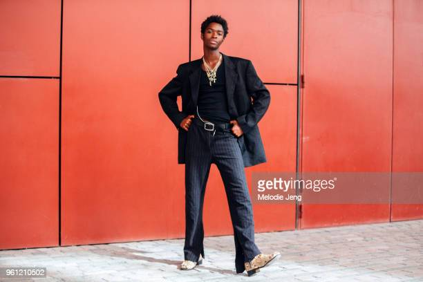 Model Alton Mason wears black pinstripe blazers pants multiple necklaces and python leather shoes during London Fashion Week Spring/Summer 2018 on...