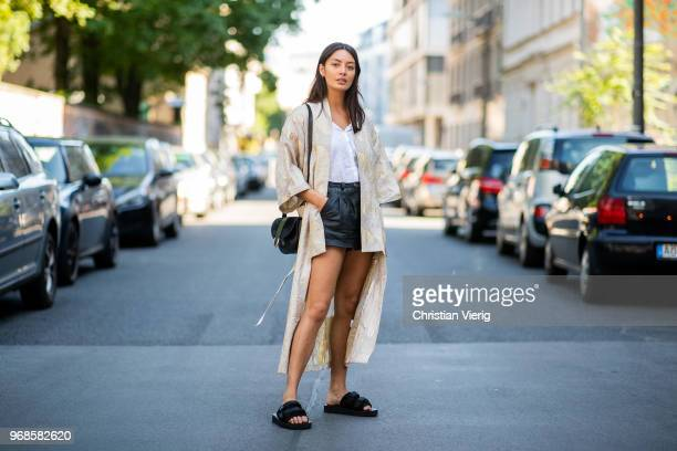 Model Alyssa Cordes wearing Gestuz kimono, slip-on Suicoke shoes, black vintage leather shorts and white blouse, black APC bag on June 6, 2018 in...