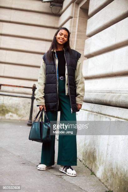 Model Alyssa Traore wears a black down vest over a cream corduroy denim jacket a black shirt wideleg green trousers a green Coach bag and Philosophy...