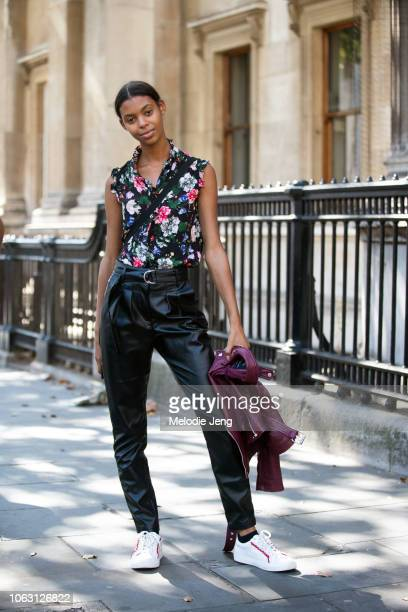 Model Alyssa Traore wears a floral Erdem top black leather pants and white Tory Sport sneakers during London Fashion Week September 2018 on September...