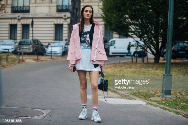 Model Amanda Googe wears a pink jacket shirt with a photograph black bag and white Fila sneakers after the Chanel and Beautiful People show during...
