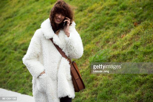 Model Ana Arto talks on the phone and wears a white teddy bear coat with a Polo Ralph Lauren messenger bag during Paris Fashion Week Menswear...