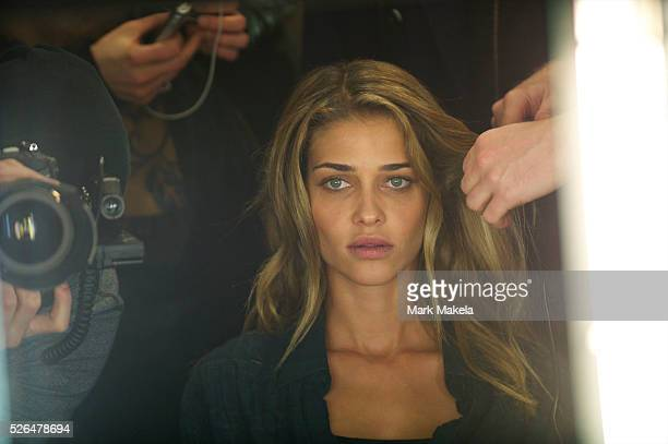 Model Ana Beatriz Barros is reflected while being styled backstage with a photographer shooting the action before the Matthew Williamson autumn 2011...