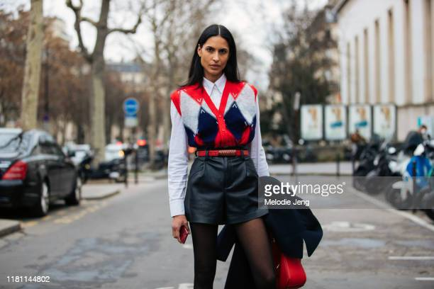 Model Ana Carolina wears a red blue and gray sleeveless cardigan white shirt red belt and bblack leather shorts outside the Atlein show at Palais de...