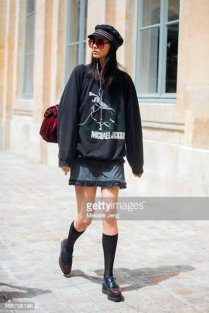 Model Ana Cristina wears a a vintage outfit including tinted sunglasses a Michael Jackson sweatshirt a red velvet purse knee high socks and platform...