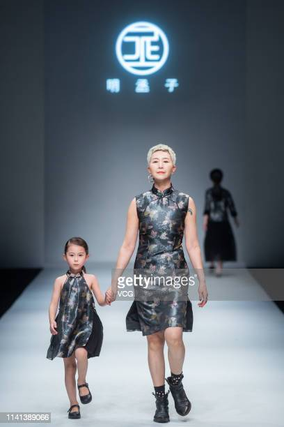 A model and a kid model showcase designs on the runway during the Mingchengzi show on day 12 of Shanghai Fashion Week 2019 A/W at 800 Show Creative...