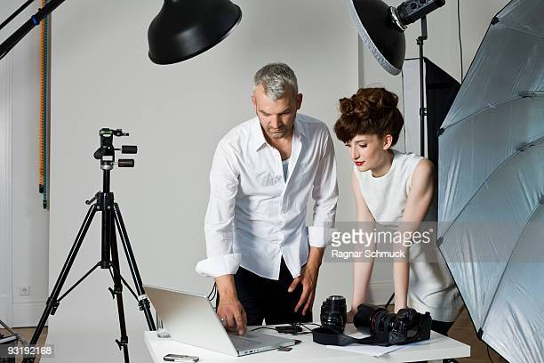 A model and a photographer looking at a laptop computer on the set of a fashion shoot