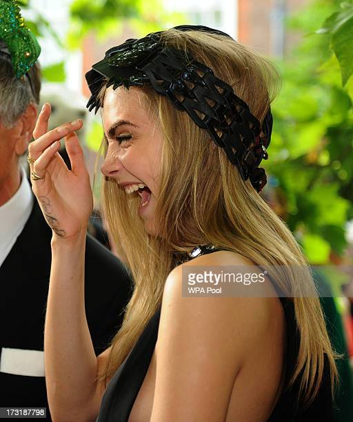 Model and actress Cara Delevingne laughs as she attends a reception hosted by Prince Charles Prince of Wales and Duchess of Cornwall a charity...