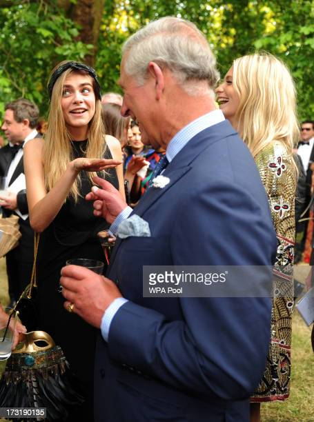 Model and actress Cara Delevingne shows off a tattoo as she meets with Prince Charles Prince of Wales as she and Poppy Delevingne attend a reception...