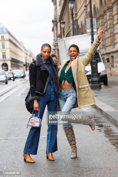 Model and artist Janaye Furman wears a denim jumpsuit, tan boots, and a cropped black shearling jacket with Model Theresa Hayes wearing a shearling...