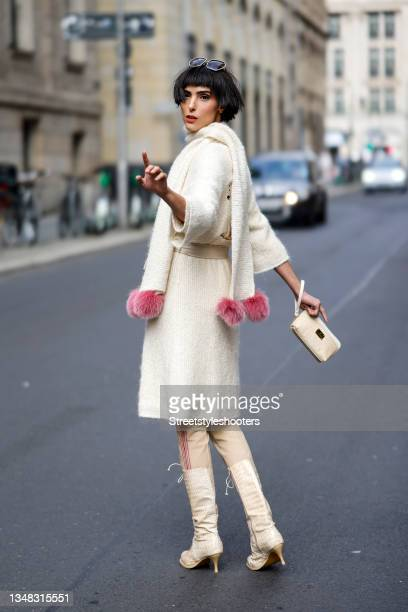 Model and artist Zoe Helali wearing a beige knitted wrap coat with polar bear embroidery by Liz Malraux, a beige knitted pullover with pink polar...