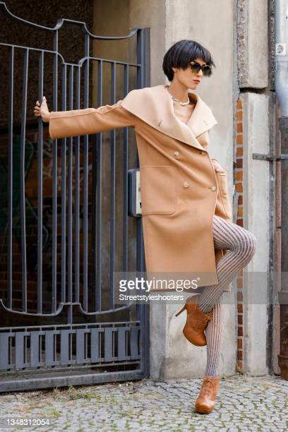 Model and artist Zoe Helali wearing a beige reversible cashmere coat by Gobi, grey striped tights by Wolford, brown ankle booties by Guido Maria...