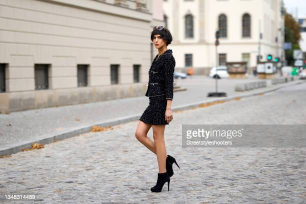 Model and artist Zoe Helali wearing a black and white boucle jacket, a matching black and white boucle mini skirt, pearl frame sunglasses by & Other...