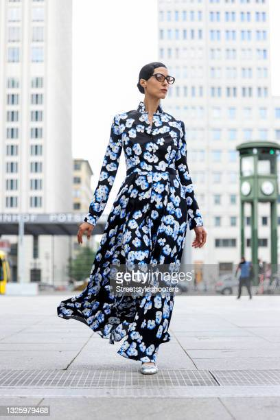 Model and artist Zoe Helali wearing a blue floral printed dress dress by Maisonnoee, jewelry by Davide Juwel, silver vintage pumps and sunglasses by...