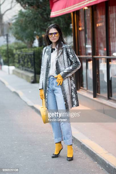 Model and blogger Doina Ciobanu wears Carrera sunglasses Nico Giani bag Miss Sixty jeans Rochas shoes and top and an I am Gia coat day 3 of Paris...