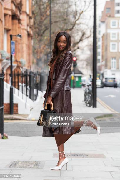 Model and Digital influencer Lauren Lemboumba wears Fenty shoes, Reformation skirt and top, Joseph coat and a Goyard bag on January 08, 2021 in...